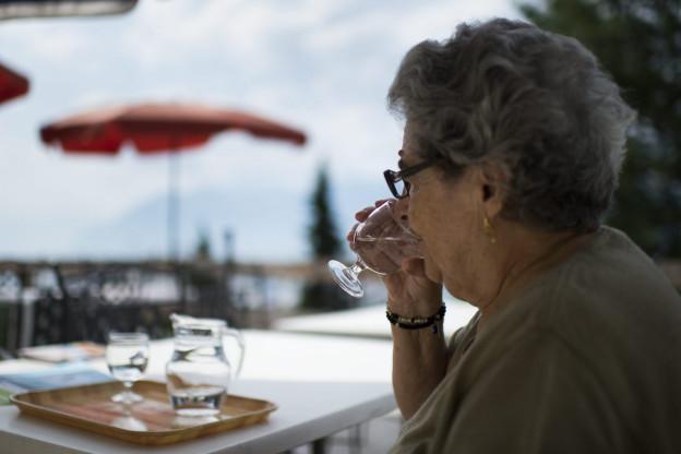 Die Sonne scheint. Eine Seniorin sitzt im Schatten und hält ein Glas Wasser in der Hand.