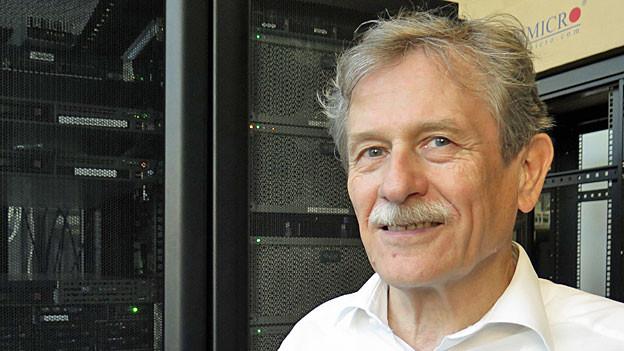 Bernhard Plattner lächelt in die Kamera. Hinter ihm eine Wand im ETH-Datacenter.