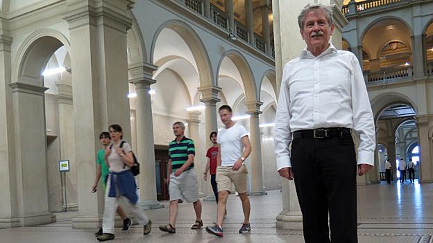 Bernhard Plattner steht in weissem Hemd und schwarzer Hose in der Eingangshalle der ETH Zürich. Hinter ihm durchqueren einige Studenten und Studentinnen die Halle.