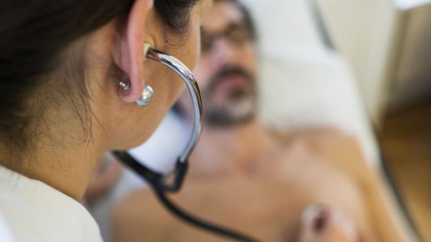 Aufnahme einer Ärztin, die einen Patienten untersucht.