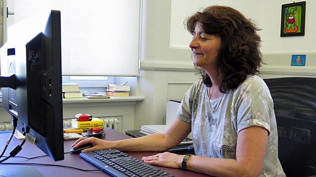 Anna Giacometti sitzt an ihrem Schreibtisch vor dem Computer.