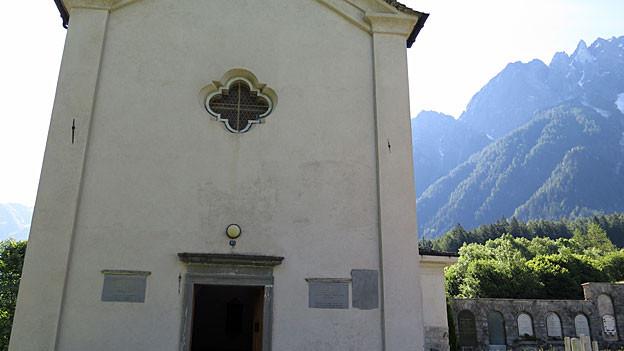 Frontansicht der schlichten, weissgetünchten Kirche neben dem Friedhof von Borgonovo. Rechts neben der Kirche ein Blick auf den Friedhof, dahinter die imposante Bergkulisse.
