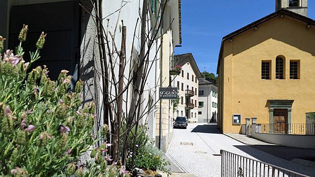Blick in die Dorfstrasse von Castasegna. Rechtss eine ockergelb gestrichene Kirche, links einige typische Steinhäuser, von einem ragt ein Schild in die Strasse, auf dem «SOGLIO» steht.