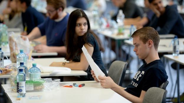 Jugendliche studieren Prüfungsaufgaben.