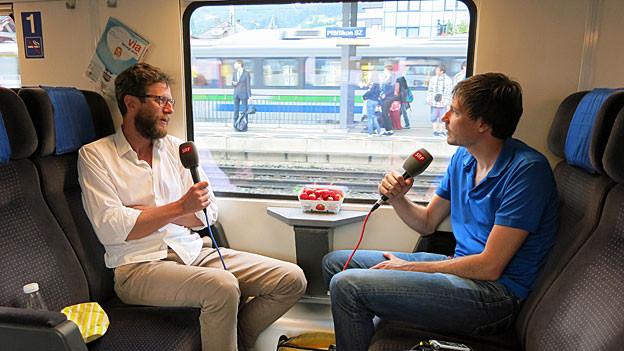 Luciano Marinello, blond, mit Bart und Brille, in sandfarbener Hose und weissem Hemd sitzt mit SRF-Redaktor Dominik Meier - er in blauen Jeans und blauem Shirt - im 1.-Klass-Abteil eines Zuges, der im Bahnhof Pfäffikon steht.