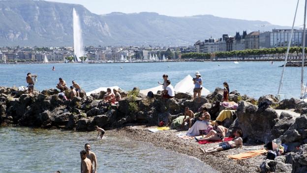 Menschen in Badehosen am Strand, dahinter der Jet d'eau von Genf