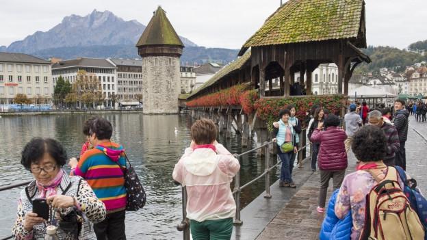 Asiatische Touristen stehen fotografierend vor der Kapellbrücke in Luzern