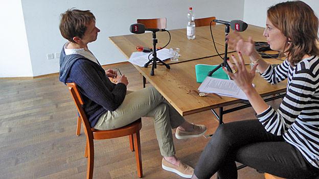 Christine Binswanger sitzt mit SRF-Inlandredaktorin an einem Tisch. Beide haben ein Mikrofon vor sich.