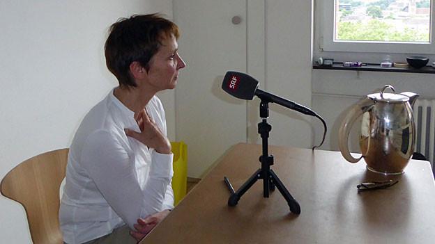 Christine Binswanger, ein weissem T-Shirt, mit kurzgeschnittenem Haar, sitzt an einem Tisch, auf dem ein Mikrophon steht.