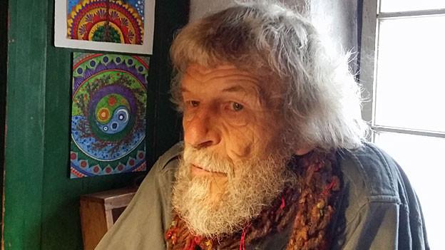 Ulrico Stamani sitzt mit dem Rücken zu einem Fenster. Braungebranntes Gesicht, weisses Haar und weisser Bart, ein rotes Tuch um den Hals. Neben ihm an der Wand hängen zwei bunte Bilder.