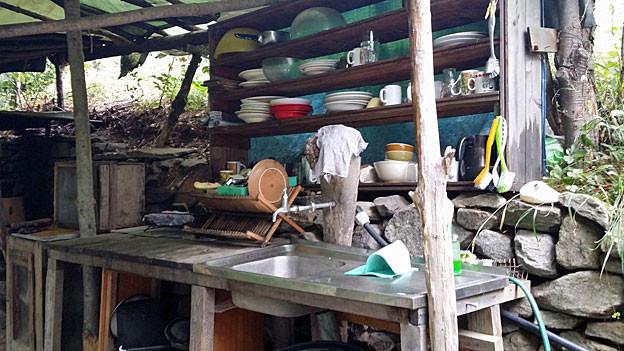 Ein Blick auf die Freiluft-Küche im Öko-Dorf. Unter einer von rohen Baumstämmen gestützten grünen Blache, steht ein Chromstahl-Schüttstein, links davon eine Abstellfläche aus Holz mit einem Abtropfständer. In einem grossen Gestell dahinter stapeln sich weisse Suppenteller und bunte «Rössler»-Kacheln.