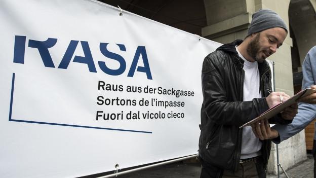Aufnahme des Rappers Greis vor einem Plakat der «RASA»-Initiative.