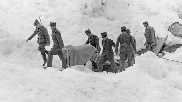 Historische Aufnahme von 1965: Soldaten tragen eine Bahre weg, auf der vermutlich eine Leiche liegt. Es liegt eine Decke über der Bahre.