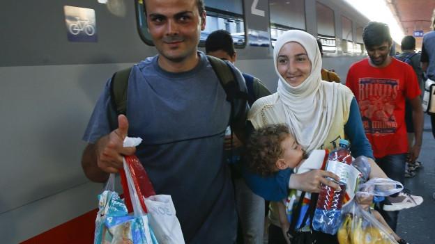 Mann und Frau mit kleinem Kind, Alle lächeln.
