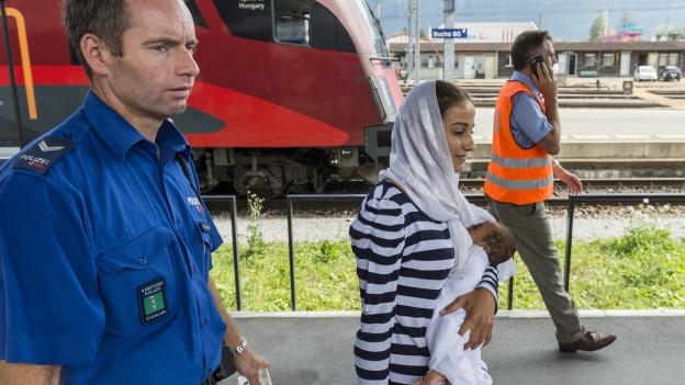 Polizist mit Frau, die ein Kind auf dem Arm trägt. Die Frau trägt ein Kopftuch.