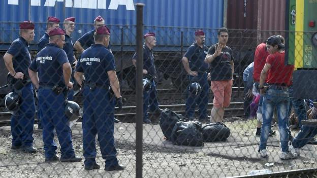 Container auf Eisenbahnwagen, um Vordergrund stehen ungarische Polizisten und Flüchtlinge, die aus einem Zug aussteigen.