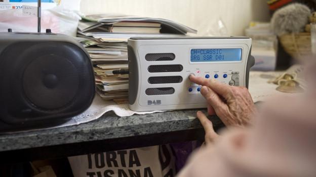 Radiogerät auf Ablage, Hand einer älteren Person dreht am Regler.
