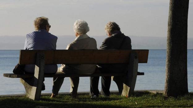 Drei ältere Frauen sitzen auf einer Bank und schauen auf einen See.