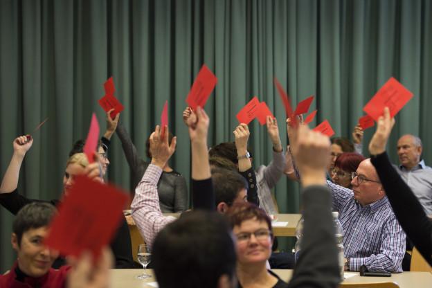 Eine Gruppe von Männern und Frauen sitzen in einem Saal und stimmen mit roten Zetteln in der Hand über die Kandidatenliste ab.