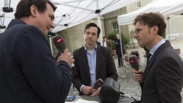 Jérôme Cosandey (Mitte) und Daniel Lampart (rechts) diskutieren im Hof des Generationenhauses in Bern..