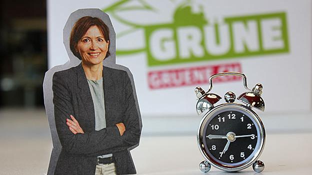 Fotomontage mit Regula Rytz links, einem Wecker rechts und im Hintergrund mit einem Plakat der Grünen Partei.