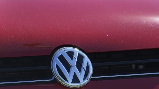 Zu sehen ist das VW-Logo auf einem Auto.