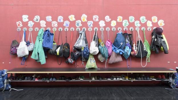 Auf dem Bild zu sehen, sind Kleider und Turnbeutel, die in einem Gang hangen im Schulhaus Am Wasser in Zürich.
