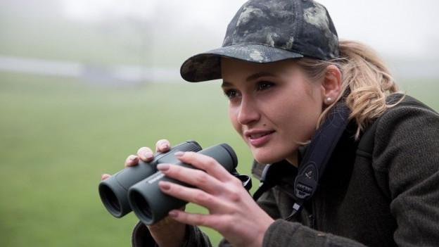 Auf dem Bild ist Kerstin Kummer, eine junge Frau, zu sehen, die mit dem Fernglas Tiere beobachtet