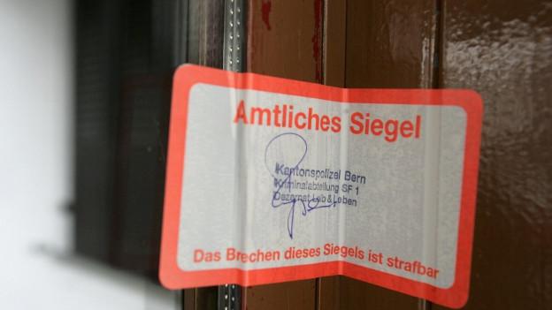 Ein amtliches Siegel klebt an der Eigangstuer eines Hotels, in dem eine Polizeirazzia stattfand.