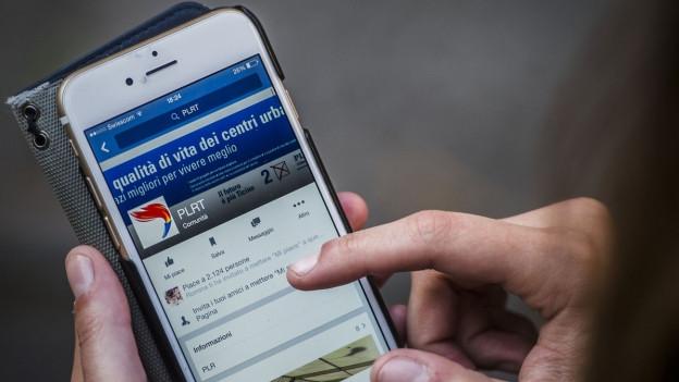 Aufnahme einer Frau, die auf ihrem Smartphone die Webseite einer Partei besucht.
