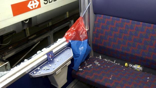 Scherben liegen auf einem SBB-Sitz neben einem eingeschlagenen Fenster.