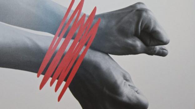 Zwei symbolisch zusammengebundene Hände - ein Symbol gegen Menschenhandel.