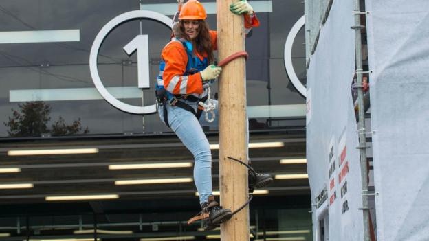 Eine Frau klettert, gesichert an einem Seil, einen Pfosten hoch.