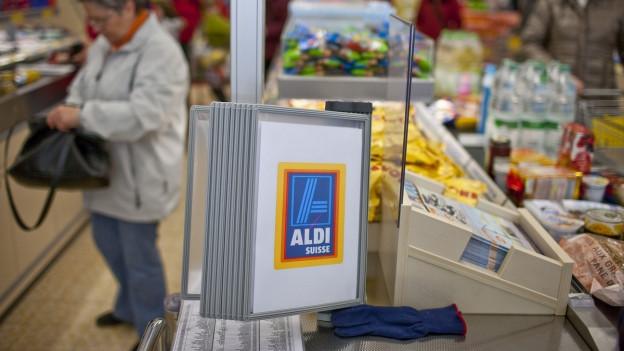 Kunden legen ihre Einkäufe vor der Kasse auf ein Band.