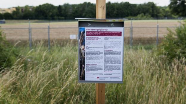 Ein Schild informiert Spaziergänger über die Versuchsart auf dem Feld hinter dem Schild.