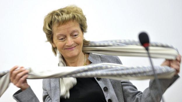 Eveline Widmer-Schlumpf steht bei einer Pressekonferenz in Genf im Januar 2012 auf dem Podium und schlingt sich schwungvoll ihren Schal um den Hals.