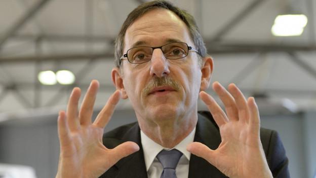Der Zürcher SP-Regierungsrat sitzt vor einem Mikrofon, hält gestikulierend die Hände in die Luft (Bild vom 6. Oktober 2015).