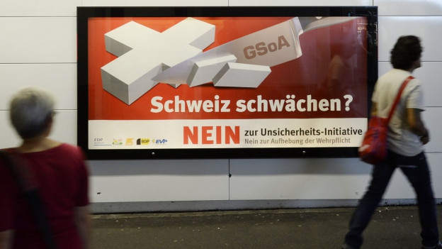 Zu sehen sind Personen, die an einem Abstimmungsplakat vorbeigehen, welches die Aufhebung der Wehrpflicht in der Schweiz thematisiert. Zuletzt sagte das Stimmvolk Im September 2013 Nein zur einer solchen Aufhebung.