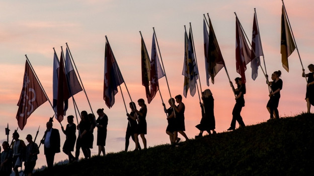 Gegenlicht aufnahme von Menschen, die im Sonnenuntergang die Fahnen von Schweizer Kantonen den Berg herunter tragen.