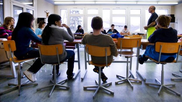 Auf dem Symbolbild sind ein Lehrer sowie Schülerinnen und Schüler im Unterricht zu sehen.