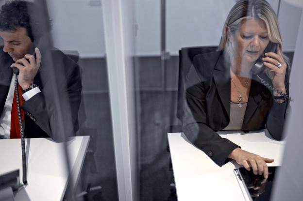 Ein Mann und eine Frau sitzen nebeneinander und telefonieren, sie sind Angestellte der UBS (Symbolbild 2012).