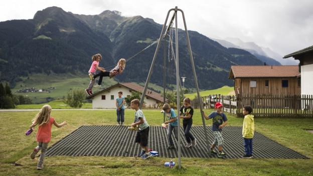 Spielende Kinder auf einer Schaukel.
