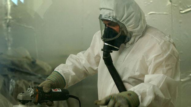 Ein Arbeiter mit Atemschutz und Schutzanzug befreit Rohre und Leitungen von Asbestrückständen.