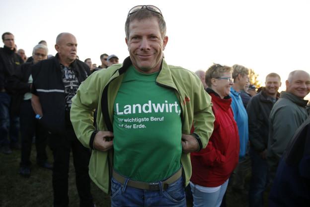 Ein Schweizer Bauer zeigt stolz sein T-Shirt.