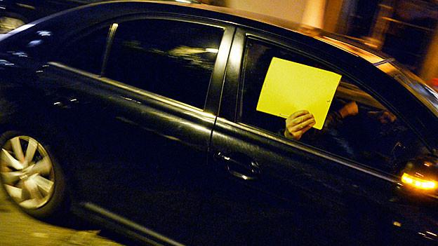 Eine Person auf dem Beifahrersitz eines schwarzen Autos der Polizeibehörden versteckt ihr Gesicht mit einem gelben Stück Papier.