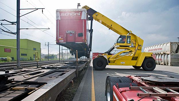Ein mobiler gelber Kran hebt einen roten Lastwagencontainer auf einen Schienentransporter.