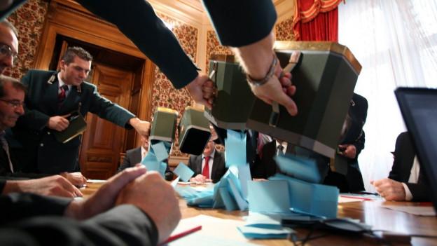 Ratsweibel leeren Stimmzettel aus den Urnen auf den Tisch der Stimmenzähler aus.