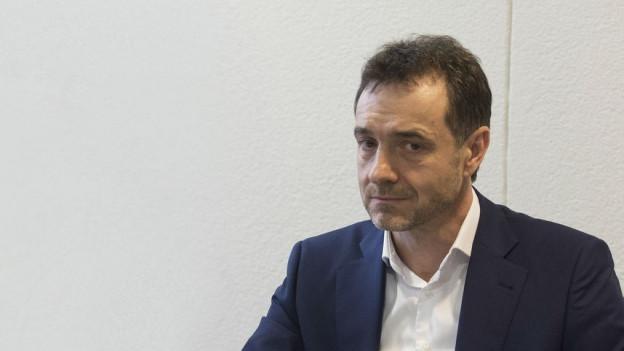 Guido Fluri, im dunkelblauen Anzug und weissen Hemd, sitzt am Tisch anlässlich einer Pressekonferenz.