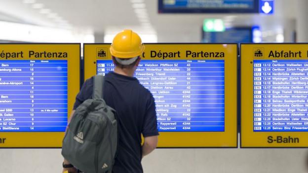 Ein Pendler studiert eine elektronische Fahrplantafel beim Bahnhof Löwenstrasse im Hauptbahnhof Zürich.