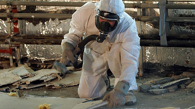 Ein Arbeiter in einem weissen Schutzanzug zerkleinert im Februar 2003 Teile von Asbestverkleidungen.